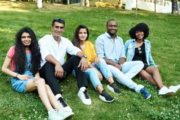 Amigos multiétnicos estão sentados na grama do parque e olhando para a câmera, sorrindo.