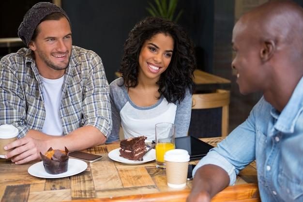 Amigos multiétnicos felizes conversando à mesa de um café