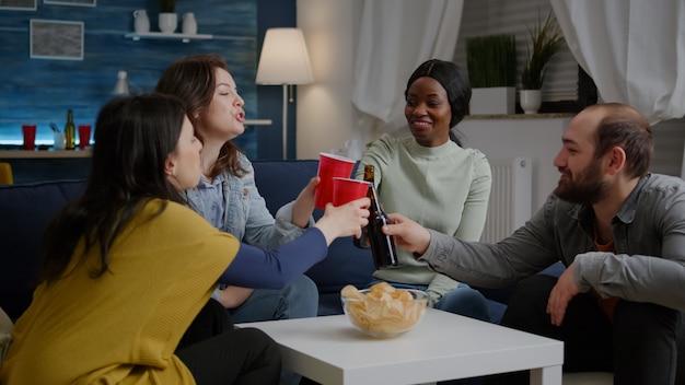 Amigos multiétnicos passando um tempo juntos, bebendo cerveja durante a festa da vida noturna, enquanto está sentado no sofá à noite na sala de estar. grupo de pessoas mestiças se divertindo, conversando