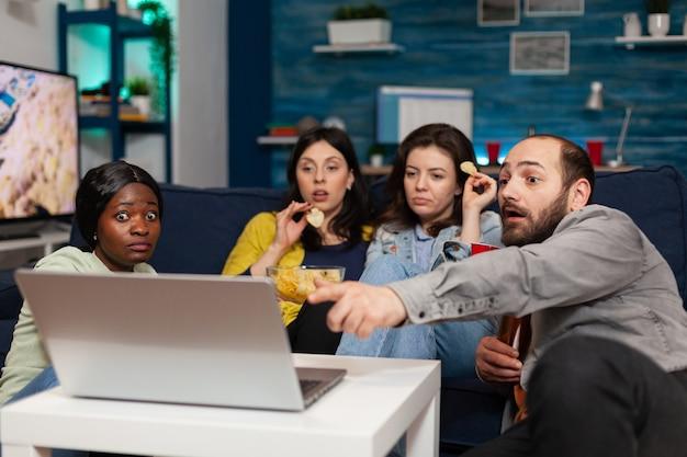 Amigos multiétnicos passando um tempo juntos olhando entretenimento no laptop, falando sobre estilo de vida. grupo de pessoas multirraciais relaxando, divertindo-se, relaxando na noite de cinema, passando um tempo
