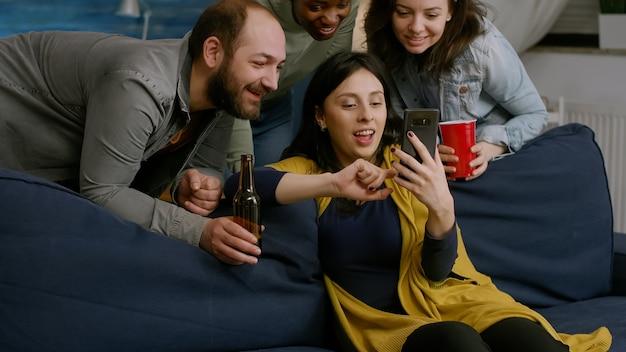 Amigos multiétnicos saindo juntos, sentados no sofá da sala, assistindo a vídeos de entretenimento ...