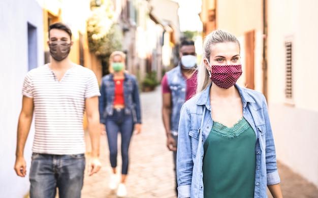 Amigos multirraciais andando com máscara facial após reabertura do bloqueio - foco seletivo na mulher certa