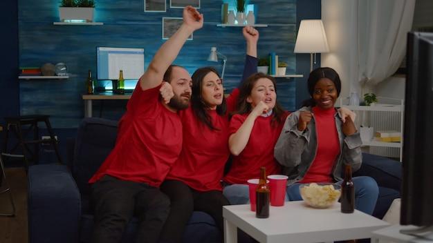 Amigos multirraciais animados comemorando time de apoio ao campeonato de futebol
