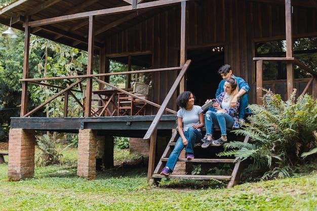 Amigos multirraciais bebendo mate em uma cabana. Foto Premium