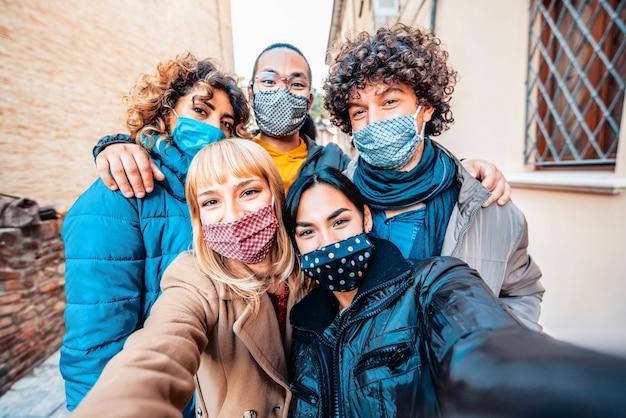 Amigos multirraciais cobertos por uma máscara facial tirando uma selfie com roupas de inverno