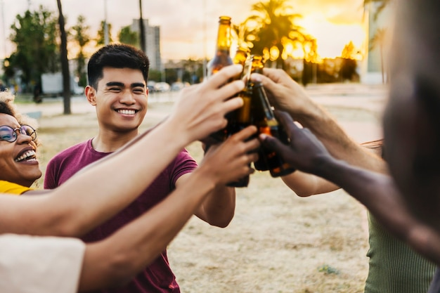 Amigos multirraciais comemorando e brindando cervejas em festa na praia