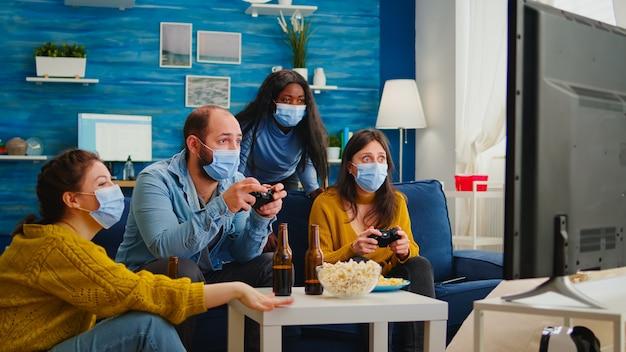Amigos multirraciais concentrados jogando videogame com controle de joystick na sala de estar usando máscara para evitar a propagação do coronavírus. diversas pessoas se divertindo, rindo de nova festa normal