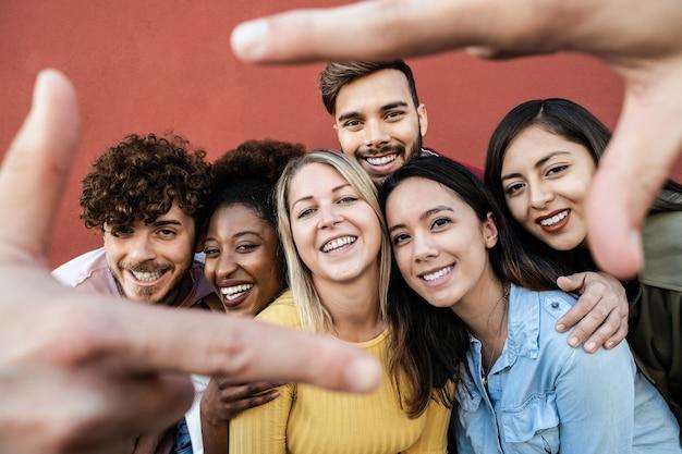 Amigos multirraciais felizes se divertindo ao ar livre - concentre-se no rosto da garota no centro