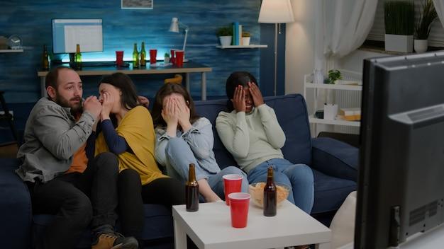 Amigos multirraciais gritando enquanto assistiam a um filme de suspense