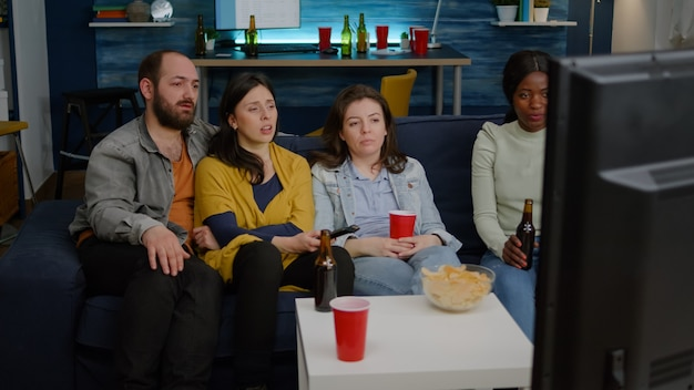 Amigos multirraciais mudando de canal na televisão até encontrarem filme engraçado