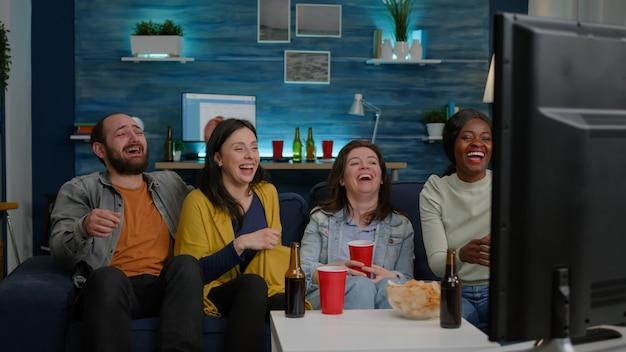 Amigos multirraciais rindo juntos enquanto estão sentados no sofá