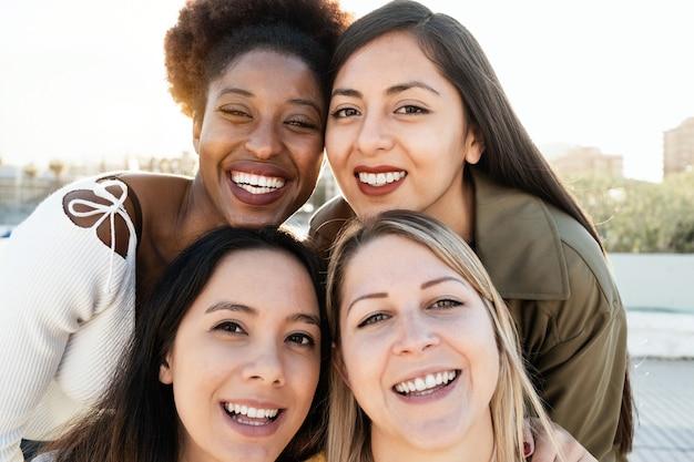 Amigos multirraciais se divertindo juntos fazendo selfie ao ar livre - concentre-se no rosto da garota africana