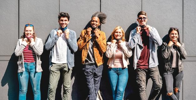 Amigos multirraciais sorrindo com máscara facial após a reabertura do bloqueio