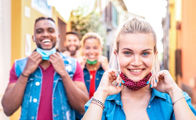 Amigos multirraciais, sorrindo com máscara facial após reabertura do bloqueio - foco seletivo na mulher certa