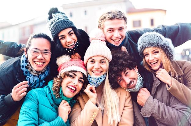 Amigos multirraciais tirando selfie com máscara facial aberta e roupas de inverno