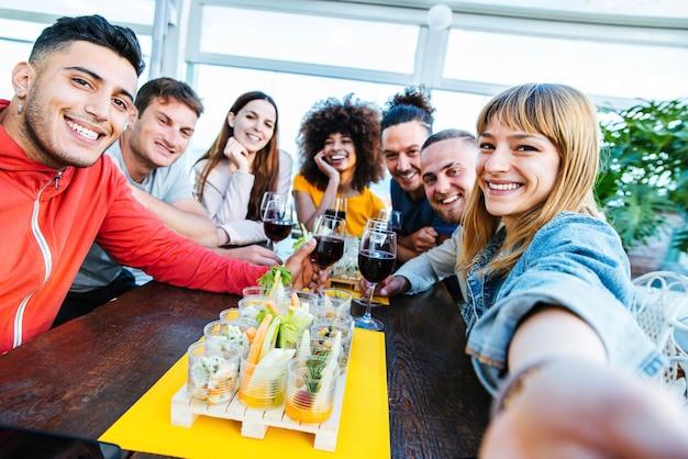 Amigos multirraciais tirando uma selfie e comemorando taças de vinho no bar