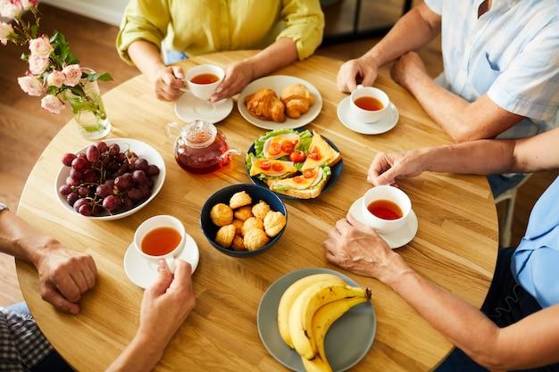 Amigos na mesa redonda com chá e lanches