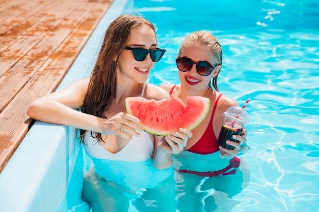 Amigos na piscina segurando uma melancia