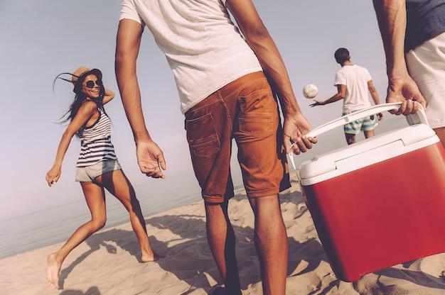 Amigos na praia. vista traseira de jovens alegres caminhando pela praia até o mar enquanto dois homens carregando refrigerador de plástico