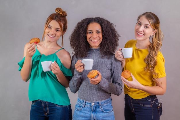 Amigos no chá da tarde comendo rosquinhas e tomando café com leite