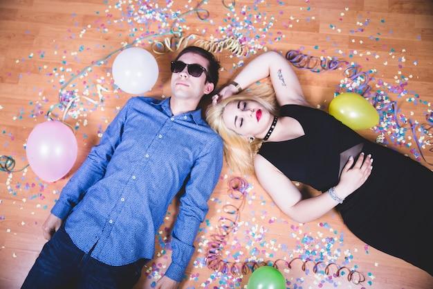Amigos no chão com confetes e balões