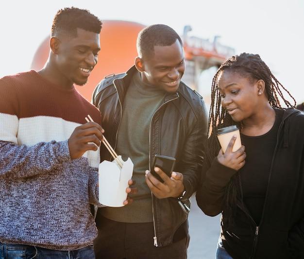 Amigos no meio de um tiro perto do food truck olhando para o telefone