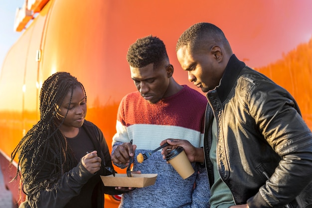 Amigos no meio do jogo comendo nuggets de frango na embalagem de comida para viagem