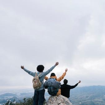 Amigos no topo da montanha, levantando os braços contra o céu nublado branco