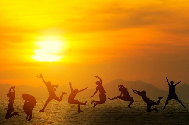 Amigos novos que têm o divertimento na praia e que saltam contra um por do sol no verão.