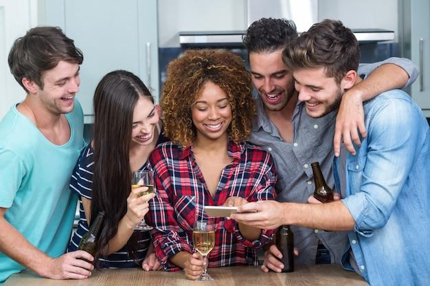 Amigos olhando no celular em pé junto à mesa