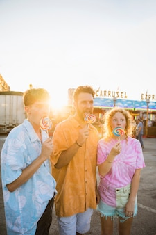 Amigos olhando para longe lambendo lollypop no parque de diversões