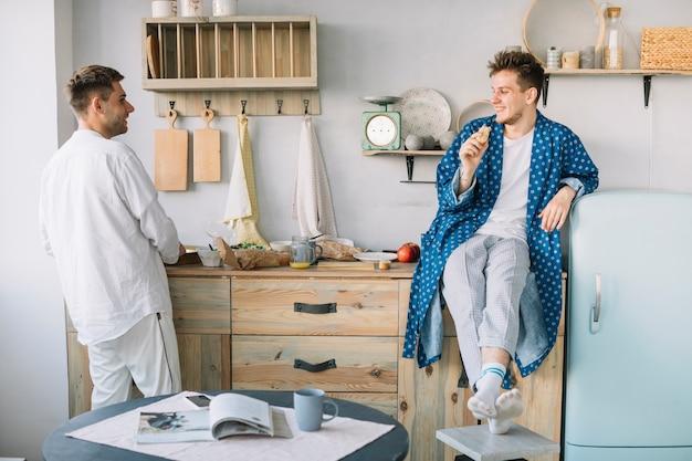 Amigos, olhando um ao outro, enquanto, alimento comendo, em, cozinha