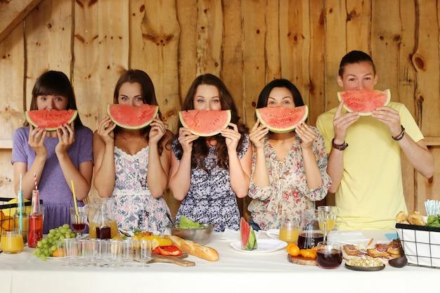 Amigos posando com fatias de melancia