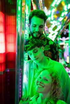 Amigos posando em luz verde no parque de diversões