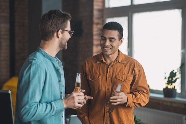 Amigos positivos e felizes se divertindo enquanto bebem cerveja juntos