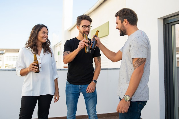 Amigos positivos felizes comemorando e brindando cerveja