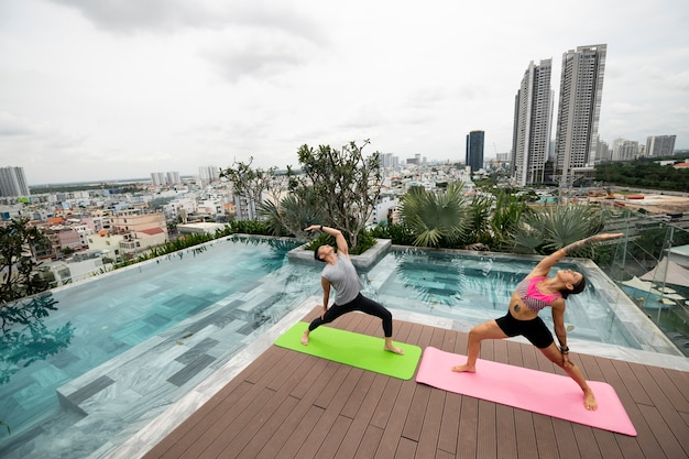 Amigos praticando ioga juntos na piscina