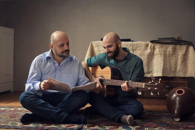 Amigos praticando tocando em uma guitarra