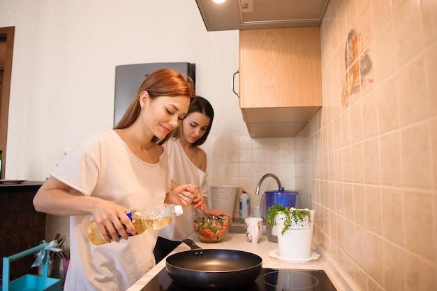 Amigos prepearing brekfast e tendo refeição na cozinha juntos.