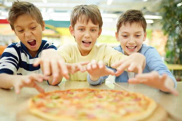 Amigos prontos para agarrar fatia de pizza