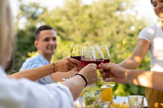 Amigos próximos a tilintar em taças de vinho
