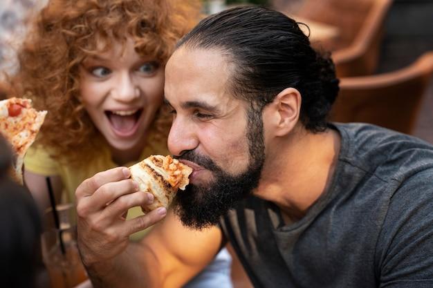 Amigos próximos comendo pizza
