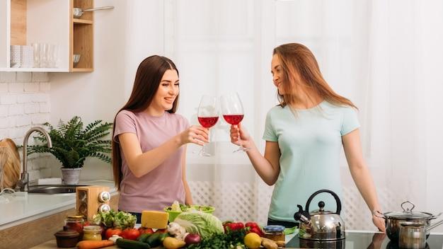 Amigos próximos. festa de menina para dois. espaço de cozinha. mulheres bonitas tilintando taças de vinho tinto.