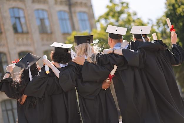 Amigos próximos. graduados usando bonés de mestrado, abraçando-se, lado a lado no pátio da universidade.
