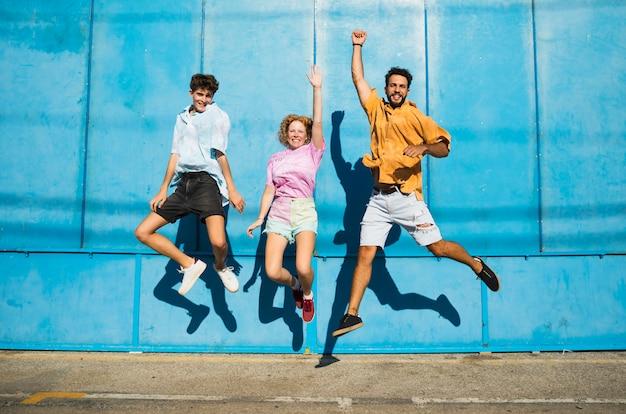 Amigos pulando com parede azul atrás