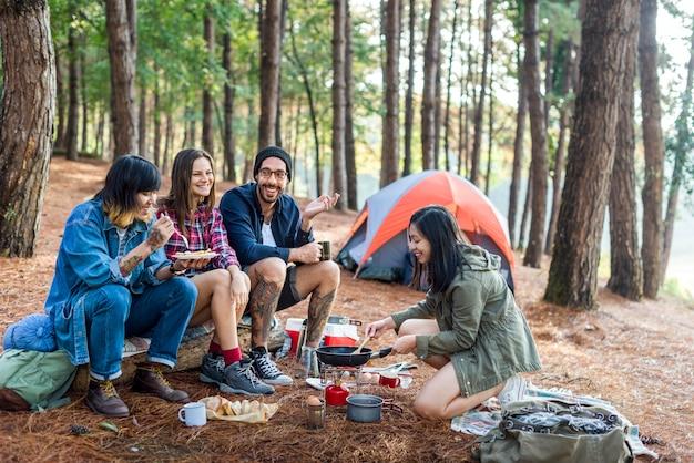 Amigos que acampam comendo o conceito do alimento