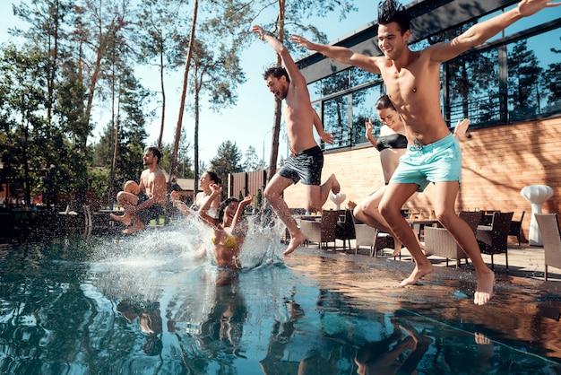 Amigos que apreciam a festa na piscina ao ar livre. conceito de férias de verão