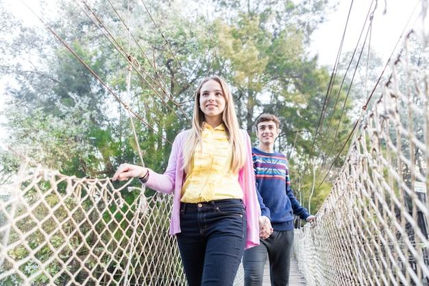 Amigos que atravessam uma ponte no parque de aventura