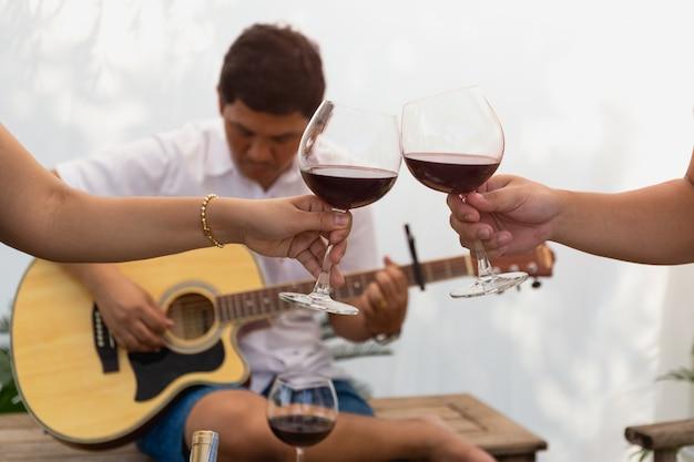 Amigos que comemoram e tocando guitarra enquanto bebe vinho tinto.