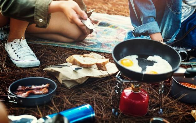 Amigos que cozinham o conceito da aventura da floresta